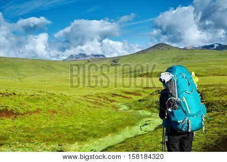 woman hiker on the trail in the Islandic mountains. Trek in National Park Landmannalaugar, Iceland. valley is covered with bright green moss