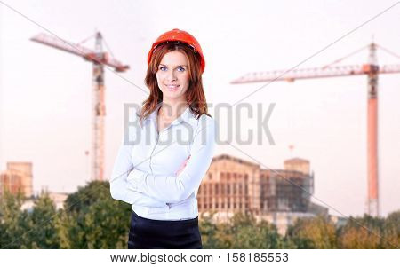 woman civil engineer on the background of building under construction.the photo has a empty space for your text