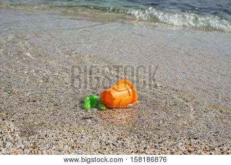 green and orange plastic toys in the seawater