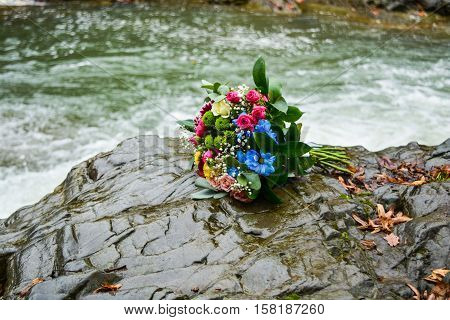 Close up of colorful wedding bouquet liening on pier of the river on rocks in mountains.