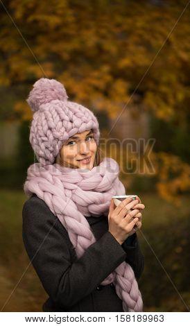 Beautiful young woman wearing merino wool pastel colors hat and scarf enjoying