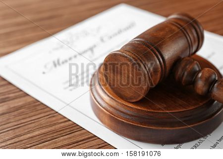 Wooden judge gavel on marriage contract, closeup