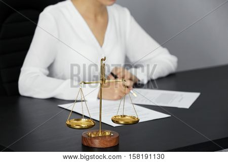 Scales of justice and businesswoman sitting at table