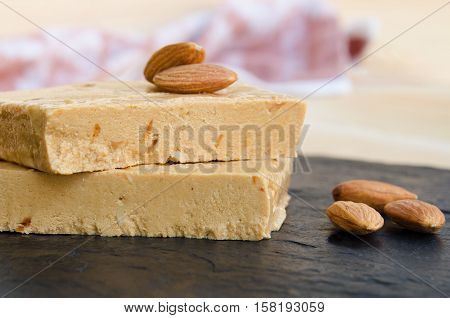Turron typical Christmas sweet in Spain. Almond nougat on black stone background.