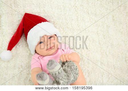 Cute baby in Santa hat lying on blanket, top view