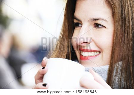 attractive happy woman having a coffee on a street with street life in winter time. Lifestyle concept