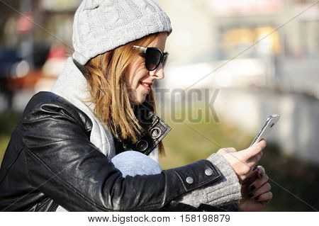Young woman sitting at the street  and using mobile phone  with street life in winter time. Lifestyle concept