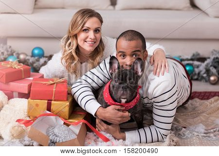 Family harmony. Nice joyful young man hugging his dog and looking at you while sitting among Christmas gifts