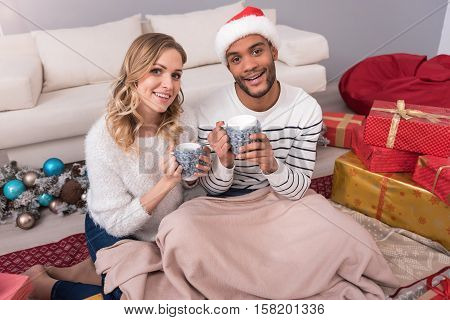 Keeping warmth. Cheerful good looking young couple sitting on the floor and covering their legs with a blanket while enjoying their tea