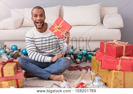 Happy New Year. Happy delighted good looking man sitting among gift boxes and holding his present while intending to open it