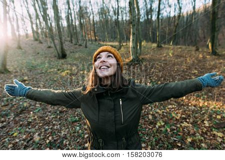 Woman with open arms in nature
