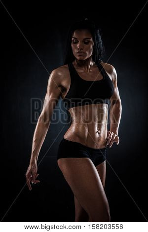 Brutal athletic woman showing abs muscles on wet background