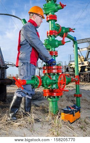 Worker in the oilfield repairing wellhead with the wrench. Pump jack background. Oil and gas concept.