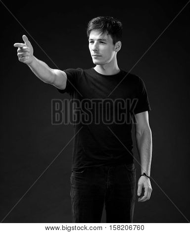 Handsome man in T-shirt pointing in one direction on a dark background