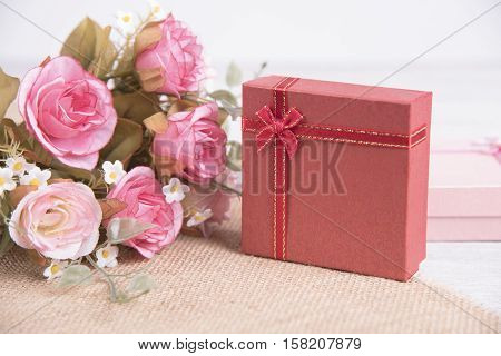 Vintage red gift box and pink rose flower on wooden background for christmas and new year.