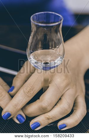 A Glass Of Grappa In Woman's Hands. Grape Brandy Or Schnapps On The Table.
