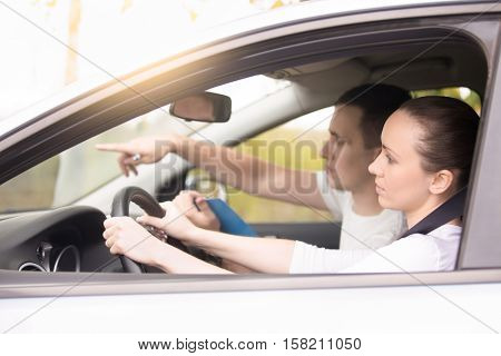 Lifestyle side view portrait of young woman driving instructed by a more skilled driver or coacher, analyzing traffic conditions, performing task