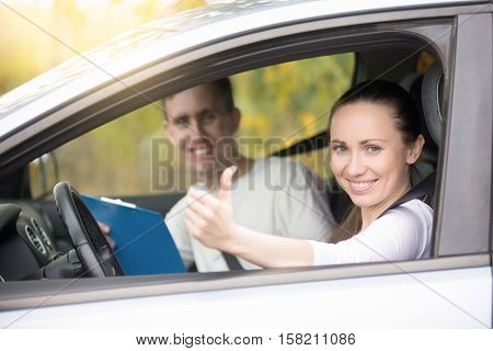 Lifestyle portrait of young happy confident lady have just finished drivers education class, showing thumb up, experienced casual instructor, holding a file folder is smiling too