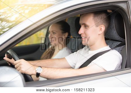 Young handsome man driving, a woman sitting near in the car, family travelling by car on summer vacation, having a pleasant weekend