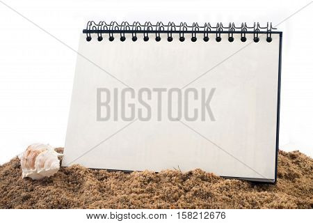 Desktop Loop wire binding book on sand and isolated white background. free space on standing book on isolated white background.