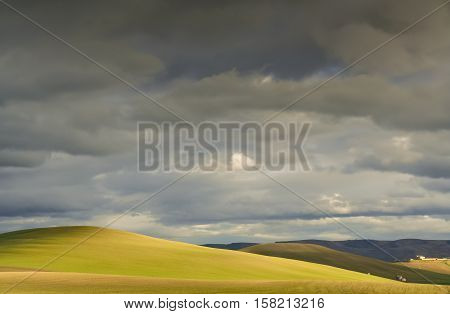 RURAL LANDSCAPE WINTER.Between Apulia and Basilicata. Hilly landscape with farmhouse dominated by thunderclouds. -ITALY- .Play of light on cultivated field dominated by thunderclouds.