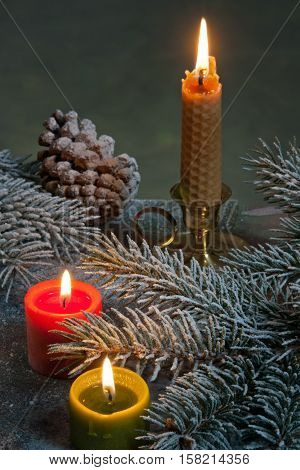 Flaming candles with Christmas twig on the Chritmas table