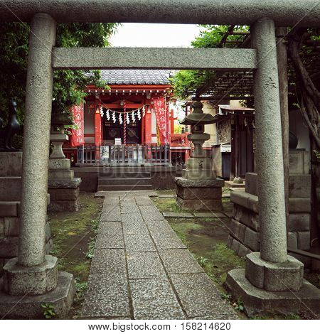 Tokyo - May 2016: Japanese wooden shrine with stone entrance gate. Nakano