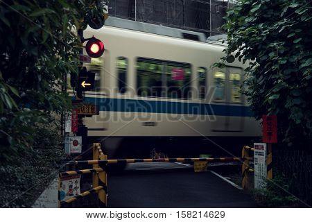Tokyo - June 2016 : Train passing by small railway crossing. Shibuya