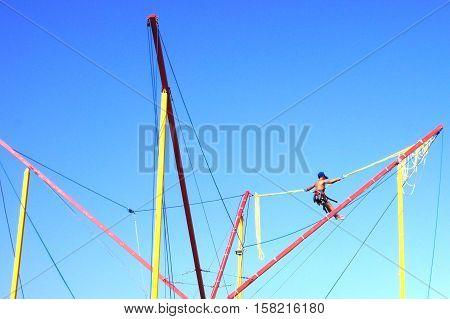 Boy swinging on a swing on blue sky background