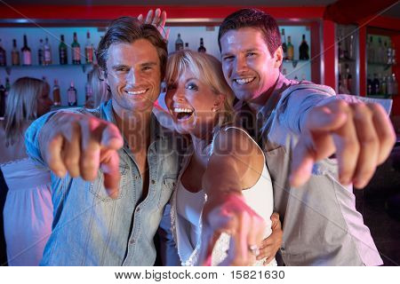 Senior Woman Having Fun In Busy Bar With Two Young Men