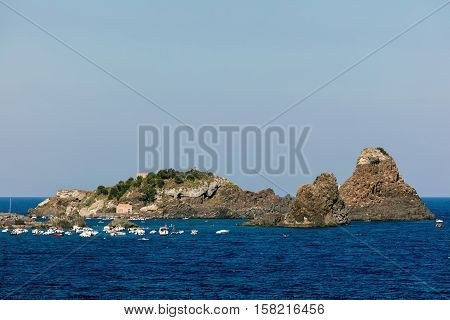 ACI CASTELLO ITALY - AUGUST 16 2016: One of the biggest attraction around Aci Castello is the Cyclops archipelago with its odd concentration of huge volcanic rocks in the Aci Trezza bay.