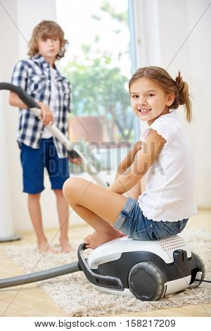 Two happy siblings doing housecleaning with vacuum cleaner