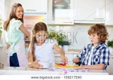 Children baking fruitcake with red currants in the kitchen