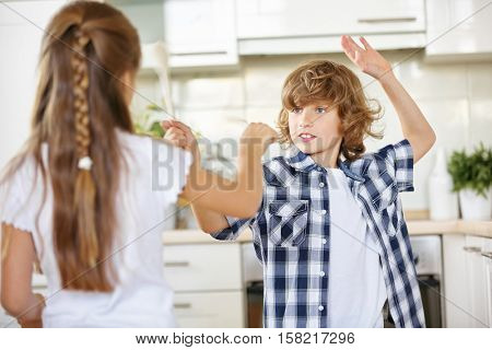 Children fighting with wooden spoons in jest in the kitchen