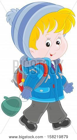 Little schoolchild in a winter jacket and a warm hat and mittens going with a schoolbag