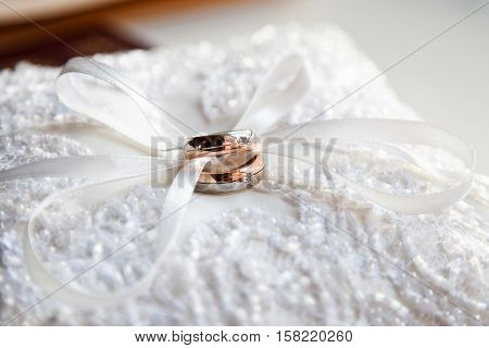 The composition of the wedding rings close up lying on a cushion