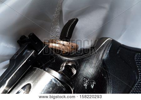 The composition of wedding rings lying trigger gun closeup