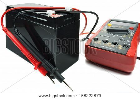 Backup battery with a multimeter and probes on a white background