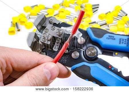Wires stripper in master hand and cord end terminals on a white background