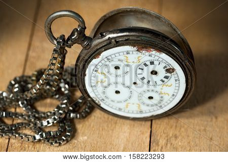 Old and vintage pocket watch with chain and without watch hands on a wooden table