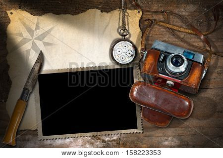 Template for adventurous travels. Old camera empty parchment photo frame broken pocket watch and a pen knife