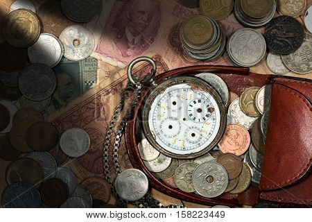 Leather purse with old coins paper banknotes and a broken pocket watch without clock hands