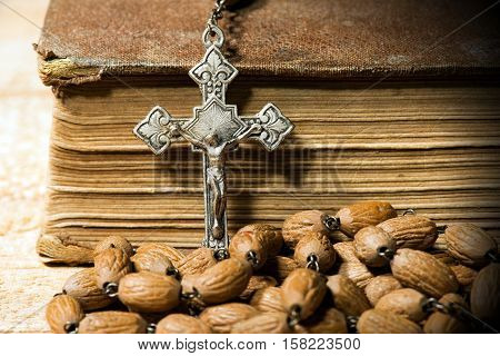 Detail of an old silver crucifix and rosary with wooden beads. On a wooden table with an old Holy Bible