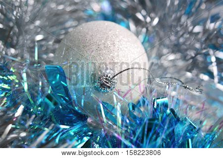 Photo by white cristmas ball in the blue and silver tinsel.