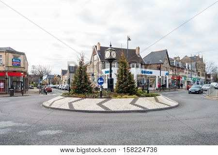 Penarth Wales United Kingdom - November 23 2016: People shopping in the town center of Penarth on a grey overcast day in November with Christmas trees at the Clock Roundabout.