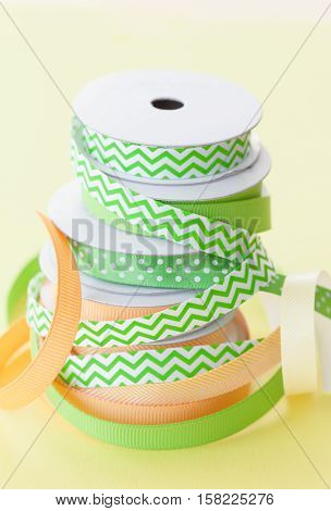 Rolls of gift ribbon stacked on a yellow background