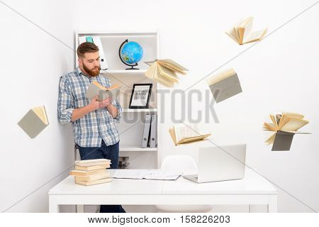 Serious bearded casual man standing and reading book in front of his workplace with flying books around