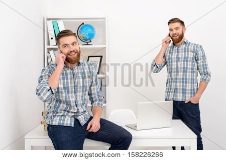 Two smiling casual business men clones talking on mobile phone in the office