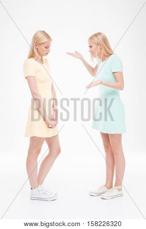 Picture of two young women swear. Isolated over white background.