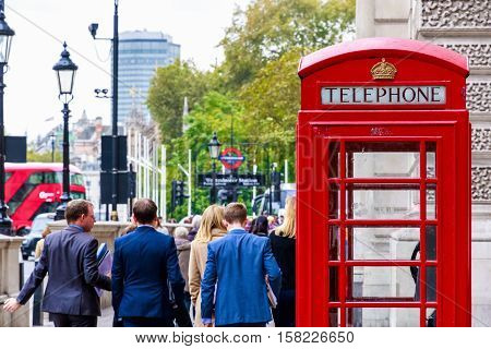 London UK - October 19 2016 - Red telephone box on London street with walking people in the background